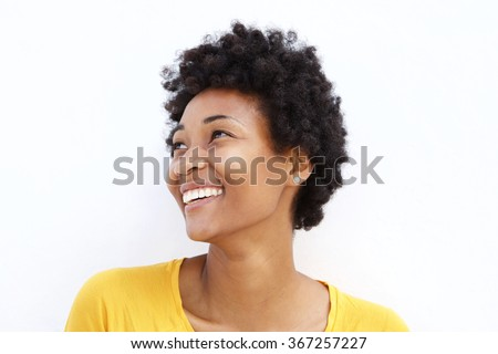 Closeup portrait of happy young african woman looking away against white background  - stock photo