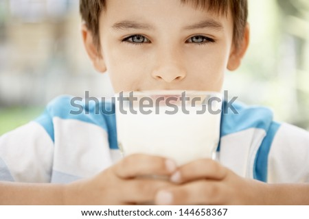 Closeup portrait of happy young boy holding glass of milk - stock photo
