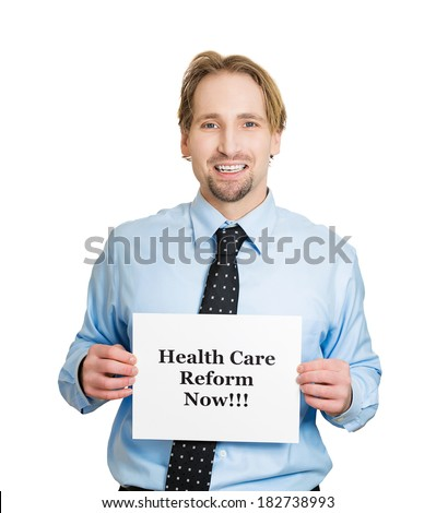 Closeup portrait of happy young business man, corporate employee holding health care reform now! sign, isolated white background. Government, federal politics, congress, insurance policy debate - stock photo