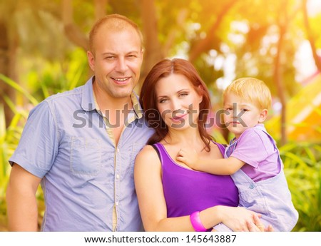 Closeup portrait of happy young family having fun outdoors, cheerful parents with adorable kid walking in the park, summer vacation - stock photo