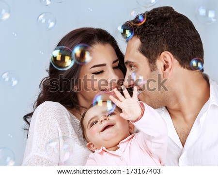 Closeup portrait of happy young family playing with soap bubbles isolated on blue background, having fun, playing game, happiness and joy concept - stock photo