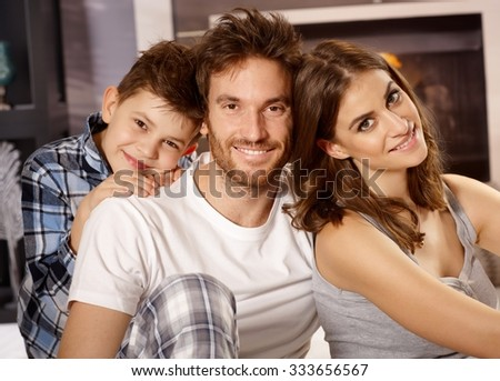 Closeup portrait of happy young family with little boy, smiling, looking at camera. - stock photo