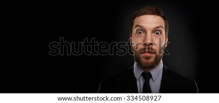 Closeup portrait of happy young handsome businessman looking shocked surprised in full disbelief open mouth eyes, on black background. Positive human emotion facial expression feeling reaction - stock photo