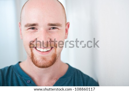 Closeup portrait of happy young man smiling isolated on bright background with copyspace - stock photo