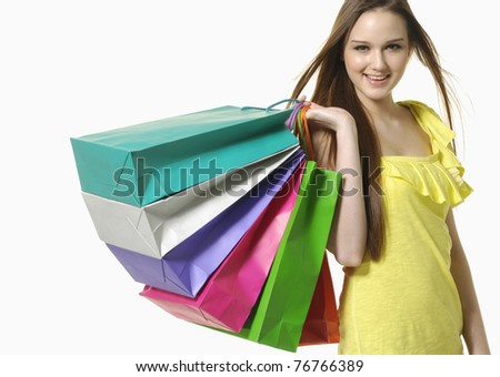 Closeup portrait of happy young woman carrying shopping bags - stock photo