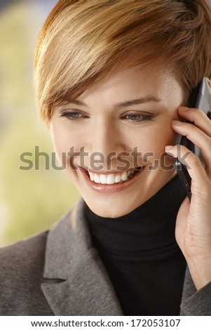 Closeup portrait of happy young woman talking on mobile phone - stock photo