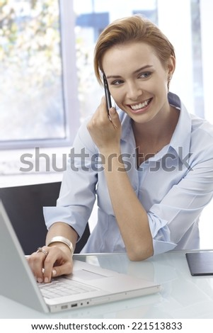 Closeup portrait of happy young woman talking on mobilephone, using laptop computer. - stock photo