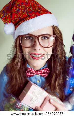 closeup portrait of holding present box funny hipster girl in sunglasses wearing Christmas Santa hat over olive copy space background, happy smiling and looking at camera  - stock photo