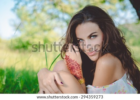 Closeup portrait of joyful glamour young pretty lady relaxing sitting on the grass and happy looking at camera - stock photo