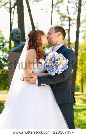 Closeup portrait of just married couple kissing in park at sunny day - stock photo