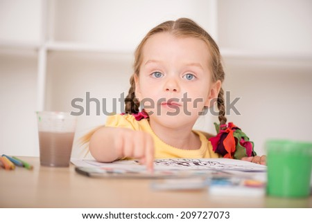 Closeup portrait of little beautiful kid, cute girl painting and pointing at her drawing with finger, pens and paints on the desk, interior shot - stock photo