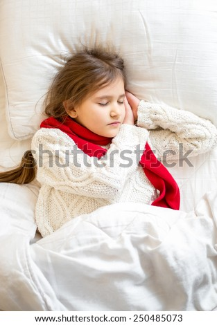 Closeup portrait of little girl in sweater sleeping at bed - stock photo
