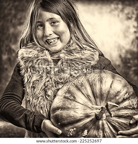 Closeup portrait of little girl posing with a big ripe pumpkin. Halloween theme. Studio shoot after freshly harvest in autumn. Sepia toned - stock photo