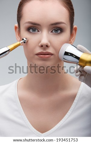 closeup portrait of lovely serene young woman and medical maniples touching her face - stock photo