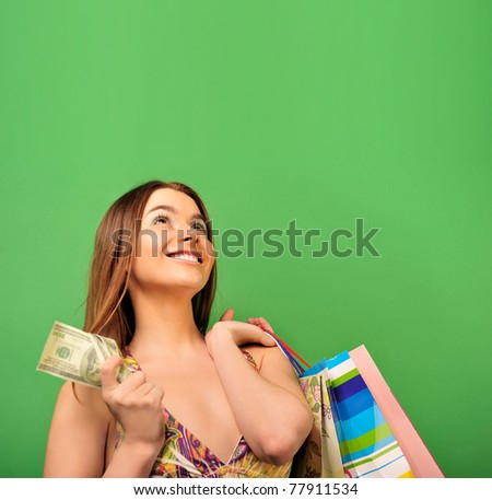 Closeup portrait of lovely woman with shopping bags over green with blank copyspace - stock photo