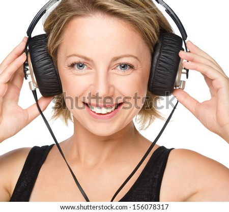 Closeup portrait of lovely young woman enjoying music using headphones, isolated over white - stock photo