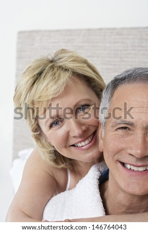 Closeup portrait of loving middle aged couple smiling at home - stock photo