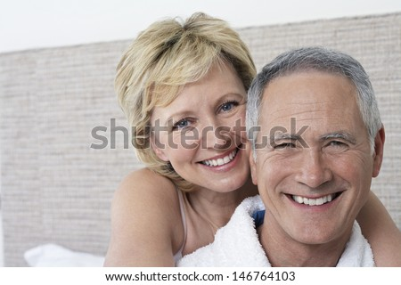 Closeup portrait of loving middle aged couple smiling in bedroom - stock photo