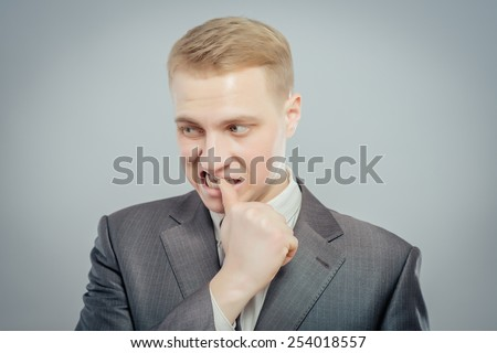 Closeup portrait of man biting his thumb fingernail or finger in mouth, very stressed and nervous, isolated on gray background with copy space - stock photo