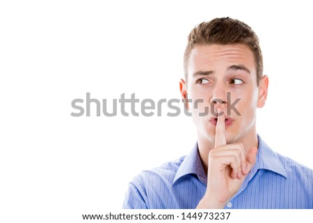 "Closeup portrait of man placing finger on lips as if to say, ""shhhhh"", ""be quiet"", ""silence"",  and looking to right with copy space isolated on white background - stock photo"