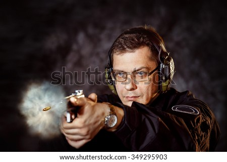 Closeup portrait of man with gun making shot at training club at dark background. - stock photo