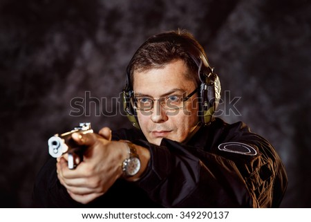 Closeup portrait of man with gun selecting aim at training club at dark background. - stock photo