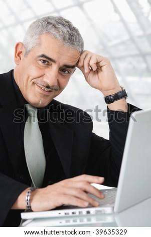 Closeup portrait of mature businessman sitting at desk, using laptop computer, smiling. - stock photo