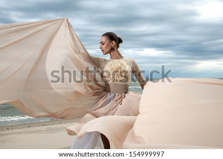 Closeup portrait of model face during posing with long dress at beach - stock photo