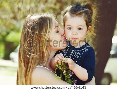 Closeup portrait of mother and cute toddler daughter - stock photo