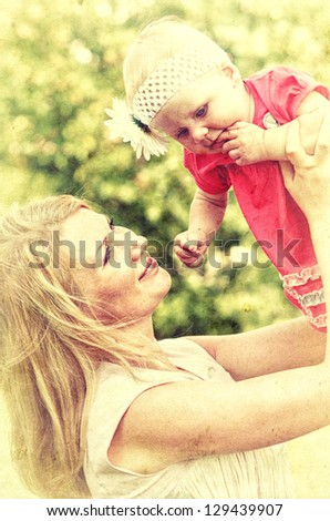 Closeup portrait of mother with her baby at outdoors. Vintage style photo. - stock photo