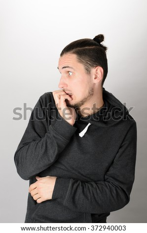Closeup portrait of nervous, stressed young nerdy guy man with eyeglasses biting fingernails looking anxiously craving something isolated on white background. Negative emotion expression feeling - stock photo