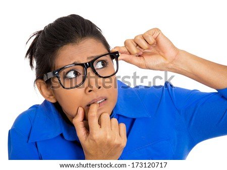 Closeup portrait of nervous, stressed young woman, girl with eyeglasses, biting fingernails looking anxiously, craving for something isolated on white background. Human emotions, expressions, feelings - stock photo