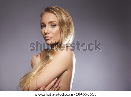 Closeup portrait of nude young woman covering her breast with hands. Sexy young female model posing against grey background. Caucasian naked young woman with copyspace. - stock photo