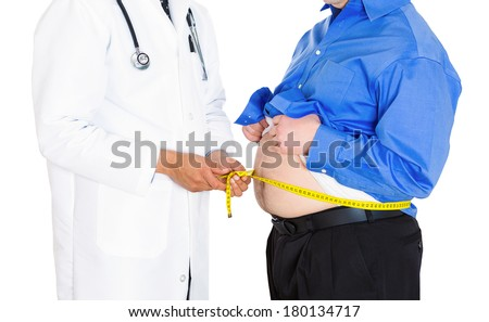 Closeup portrait of obese, overweight male patient, doctor measuring with tape his waist line around stomach, belly isolated on white background. Patient health care, weight reduction program concept - stock photo