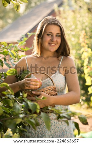 Closeup portrait of of beautiful smiling woman holding basket with apples at garden - stock photo
