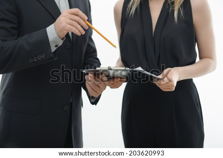 Closeup portrait of office workers holding clipboard and pencil, discussing something, isolated on white - stock photo