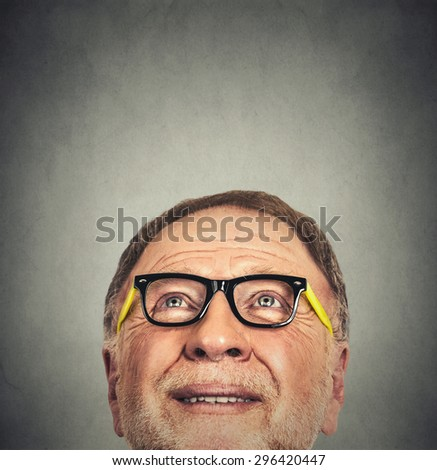 Closeup Portrait of Old Man with glasses looking up isolated on gray wall background with copy space  - stock photo