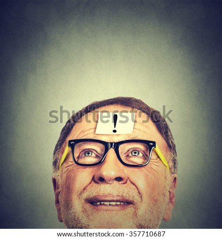 Closeup portrait of old thinking man with glasses and exclamation sign mark on forehead looking up isolated on gray wall background with copy space. Positive face expression  - stock photo