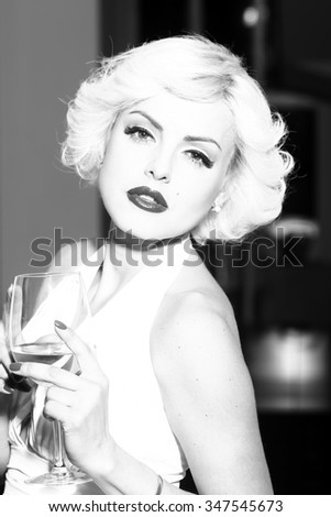 Closeup portrait of one attractive sensual smiling sexy young retro woman with blonde hair bright lips in dress in monroe style indoor with glass of wine black and white, vertical picture - stock photo