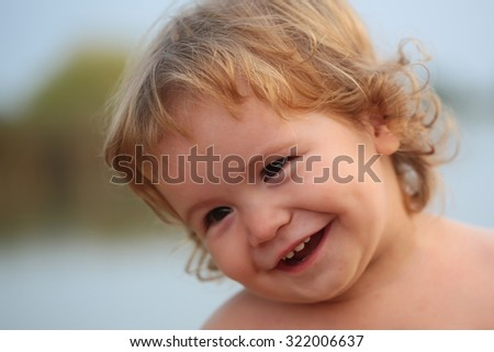 Closeup portrait of one cute funny playful happy emotional smiling little boy with blonde curly hair and round cheeks looking away outdoor on natural background, horizontal picture - stock photo