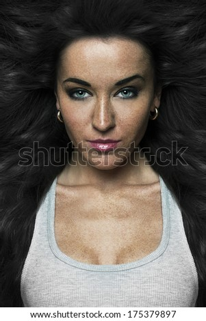 Closeup portrait of passionate woman with flaring hair, alluring eyes and open neckline. - stock photo
