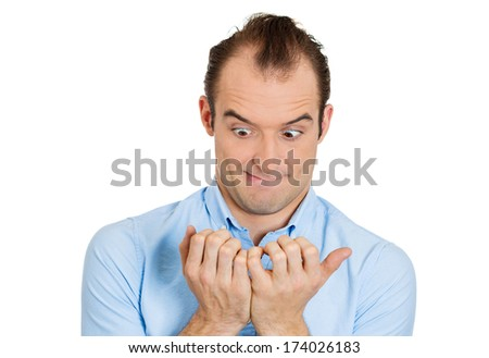 Closeup portrait of perfectionist man, obsessive compulsive, agitated young guy, anxiously staring at his fingernails, making sure they are clean, isolated on white background. Human face expressions - stock photo