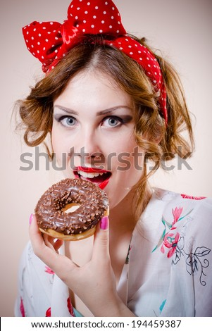 closeup portrait of pinup girl beautiful blond young woman with excellent dental care teeth having fun eating donut happy smiling & looking at camera on white background - stock photo