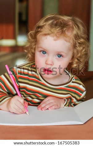 Closeup portrait of preschooler with strawberry blonde curly hairs who draws in the sketchbook by pencil and looks into the lens - stock photo