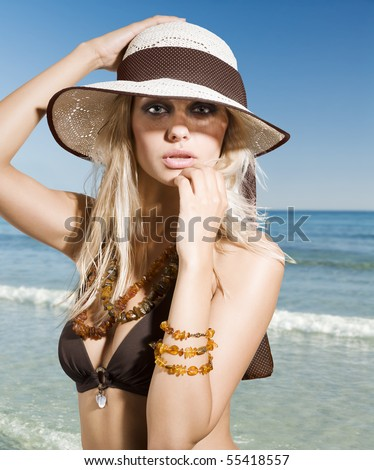 closeup portrait of pretty blond woman wearing a nice summer hat - stock photo