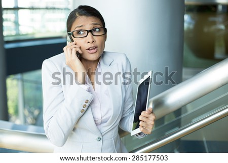 Closeup portrait of pretty busy woman in gray suit and pink shirt holding phone and tablet, sorry and apologizing for her mistakes, caught red-handed, isolated indoors office background - stock photo