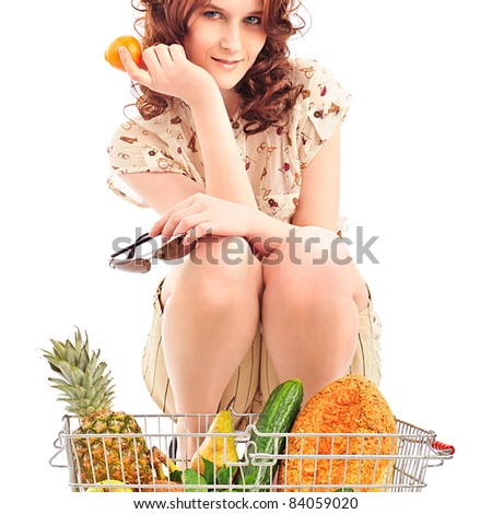 Closeup portrait of pretty caucasian woman wearing stylish clothes and sunglasses with shopping basket full of fresh vegetables, fruits, bread and other grocery products isolated on white background - stock photo