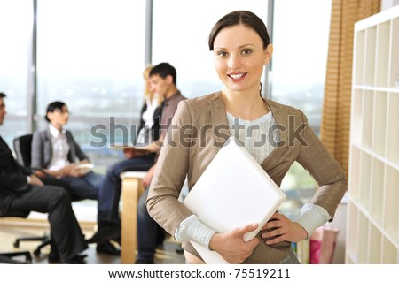 Closeup portrait of pretty cheerful business woman in an office environment holding laptop. Large panoramic window on background - stock photo