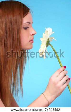 Closeup portrait of pretty young female sniffing white flower - stock photo