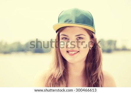 Closeup portrait of pretty young smiling woman on outdoor park lake city background  - stock photo